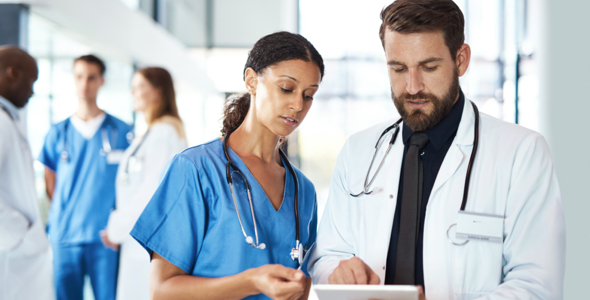 two medical professionals, one male and one female, looking at a chart