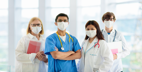 Four doctors standing side by side wearing masks